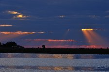 Shafts of the last light beaming through thick clouds over the Chobe river.CNP boat on the Chobe at sunset.